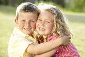 2 παιδιά που αγκαλιάζει σε εξωτερικούς χώρους — Φωτογραφία Αρχείου