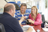 Couple filling in paperwork in car showroom — Stockfoto