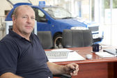 Car salesman sitting in showroom — Stock Photo