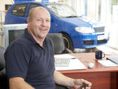 Car salesman sitting in showroom smiling — Stock Photo