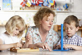 Adult Helping Two Young Children at Montessori/Pre-School — Stock Photo