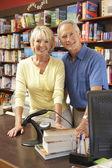 Couple running bookshop — Stock Photo