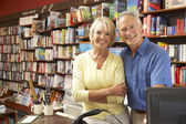 Couple running bookshop — Stock Photo
