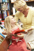 Grandmother and grandaughter in bookshop — Stock Photo