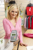 Female sales assistant in clothing store — Stock Photo