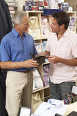 Customer in clothing store with sales assistant — Stock Photo