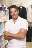 Male sales assistant in clothing store — Stock Photo
