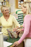 Sales assistant with customer in health food store — Stock Photo