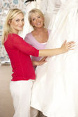 Bride trying on wedding dress with sales assistant — Stock Photo