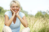 Portrait of mature woman sitting in countryside — Stock Photo
