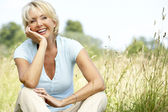 Portrait of mature woman sitting in countryside — Stockfoto