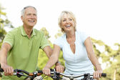 Mature couple riding bikes — Stock Photo