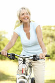 Portrait of mature woman riding cycle in countryside — Stock Photo