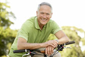 Portrait of man riding cycle in countryside — Stock Photo