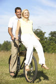 Young couple riding bike in countryside — Stock Photo
