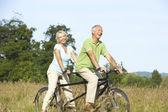 Mature couple riding tandem — Stock Photo