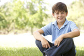 Portrait Of Young Boy Sitting In Park — Stock Photo