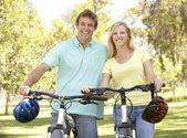 Giovane coppia sul ciclo cavalcare nel parco — Foto Stock