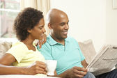 Couple Relaxing At Home With Newspaper — Stock Photo