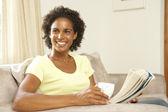Mujer leyendo libro con copa en casa — Foto de Stock