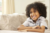 Young Boy Relaxing On Sofa At Home — Stock Photo