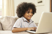 Young Boy Using Laptop At Home — Stok fotoğraf