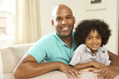 Father And Son Relaxing On Sofa At Home — Stock Photo
