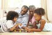 Grandparents Playing Board Game At Home With Grandchildren — Stock Photo
