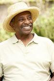 Bahçe içinde gülümseyen kıdemli adam — Stok fotoğraf