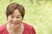 Portret van glimlachen senior vrouw buitenshuis — Stockfoto
