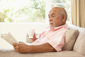 Senior Man Reading Book With Drink At Home — Stock Photo