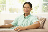 Young Man Relaxing On Sofa At Home — Stock Photo