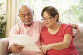 Senior Couple Discussing Document At Home — Stock Photo