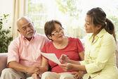 Couple de personnes âgées parler à un conseiller financier à la maison — Photo