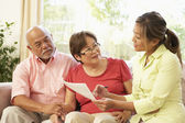 Senior koppel praten met financieel adviseur thuis — Stockfoto