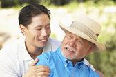 Senior hombre con hija adulta en jardín — Foto de Stock
