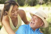 Uomo anziano con una figlia adulta in giardino — Foto Stock