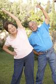 Senior Couple Exercising In Garden — Stock Photo