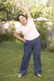 Senior Woman Exercising In Garden — Stock Photo