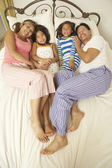 Young Family Relaxing In Bedroom — 图库照片