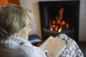 Senior Woman Reading Book By Fire At Home — Stockfoto