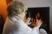 Senior Woman Warming Hands By Fire At Home — Stock Photo