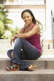 Genç kadın binası merdivenlerinde oturmuş — Stok fotoğraf