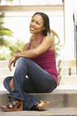 Young Woman Sitting On Steps Of Building — Stock Photo