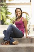 Mladá žena sedí na schodech budovy — Stock fotografie