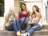 Three Girlfriends Sitting On Steps Of Building — Stock Photo