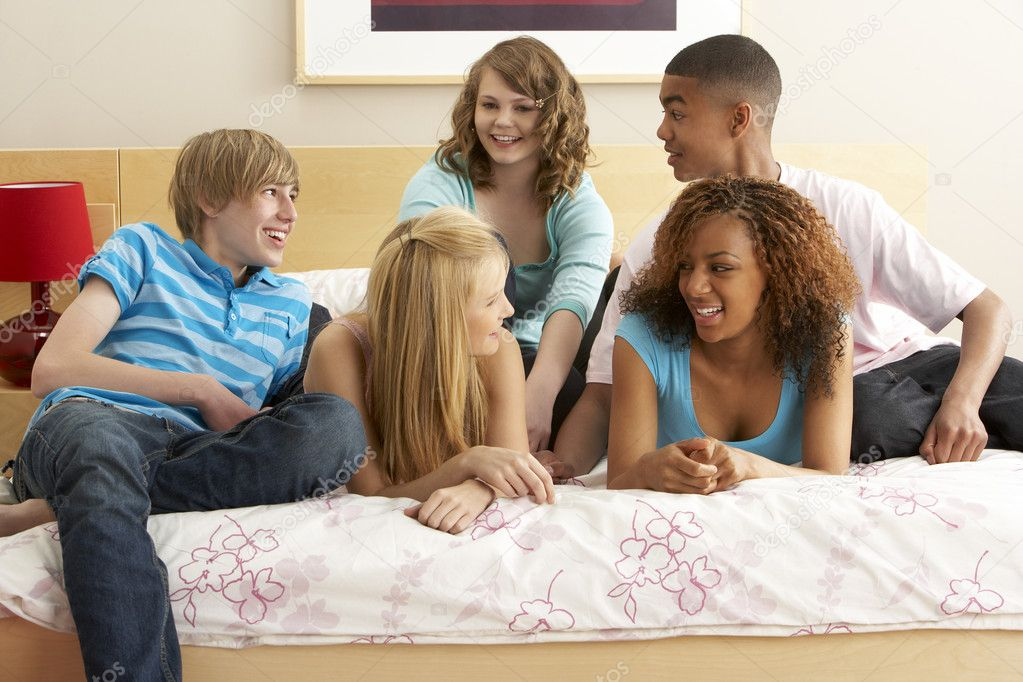 Group of five teenage friends hanging out in bedroom for Hanging groups of pictures
