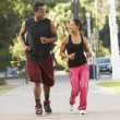 Young Couple Jogging On Street - Foto Stock
