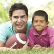 Stock Photo: Father And Son In Park With AmericFootball