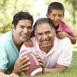Stock Photo: Grandfather With Son And Grandson In Park With AmericFootball